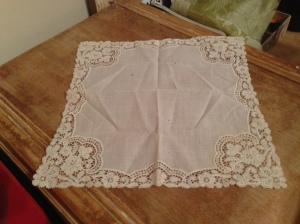 Pink cotton handkerchief with lace edges.